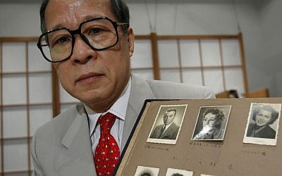 FILE - In this July 26, 2010 file photo, Akira Kitade holds a photo album that belonged to a former colleague of his at the Japan Tourist Bureau, Tatsuo Osako, during an interview in Tokyo. The page displayed holds seven photos given to Osako by people whom Osako helped escape from Europe in the early days of World War II. (Shizuo Kambayashi/AP)