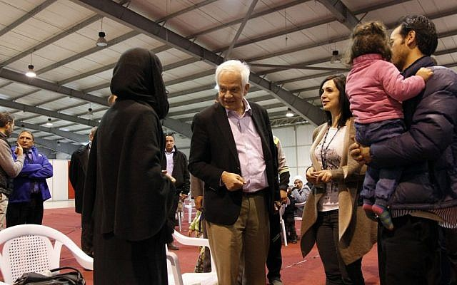 Canadian Minister of Immigration John McCallum, center, talks to a Syrian family soon to be resettled in Canada, Sunday, Dec. 20, 2015, at an airport in Amman, Jordan. (AP Photo/Sam McNeil)
