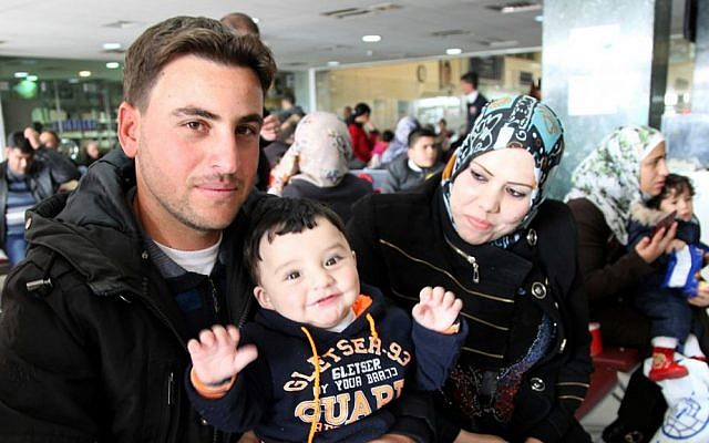 Radi poses for a photo with his son and wife, whose names are omitted for security reasons, while waiting in an airport in Amman, Jordan, to board a plane to Canada where they will be resettled, December 20, 2015. (AP/Sam McNeil)