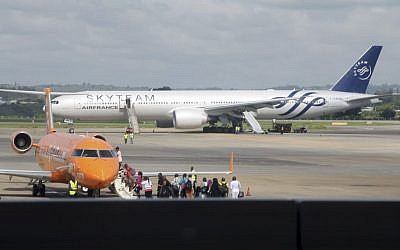An Air France plane which made an emergency landing is seen behind passengers boarding on a small jetliner at Moi International Airport in Mombasa, Kenya Sunday, Dec. 20, 2015.(AP Photo/Edwin Kana)