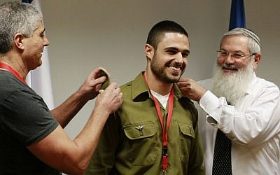 Deputy Defense Minister Eli Ben Dahan, right, and Asher Morag, left, present the rank of first lieutenant to Aviv Morag, an IDF soldier who was cleared of all charges in connection to the death of a Palestinian man in 2013, during a ceremony in Ben Dahan's office on December 17, 2015. (Judah Ari Gross/Times of Israel)
