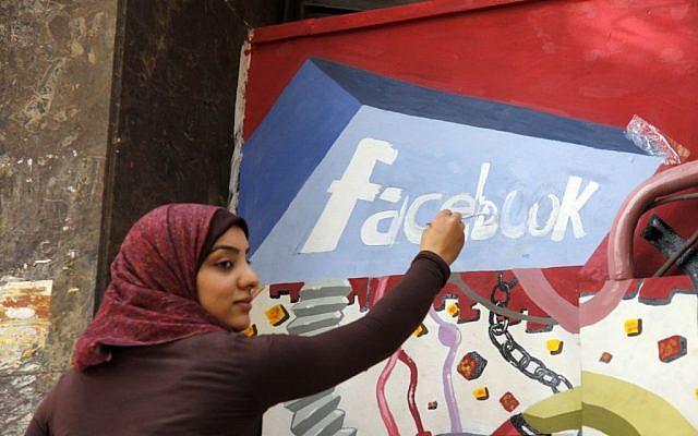 An art student from the University of Helwan paints the Facebook logo on a mural commemorating the revolution that overthrew Hosni Mubarak in the Zamalek neighborhood of Cairo, Egypt, March 30, 2011. (AP Photo/Manoocher Deghati, File)