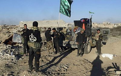 Iraqi security forces enter the heavily damaged Huz neighborhood in downtown Ramadi, 70 miles (115 kilometers) west of Baghdad, Iraq, Saturday, Dec. 26, 2015. (AP Photo/Osama Sami)