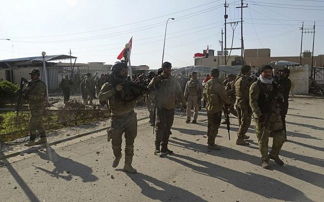 Iraqi security forces enter the government complex in central Ramadi, 70 miles (115 kilometers) west of Baghdad, Iraq, Monday, Dec. 28, 2015. Iraqi military forces on Monday retook a strategic government complex in the city of Ramadi from Islamic State militants who have occupied the city since May. (AP/Osama Sami)