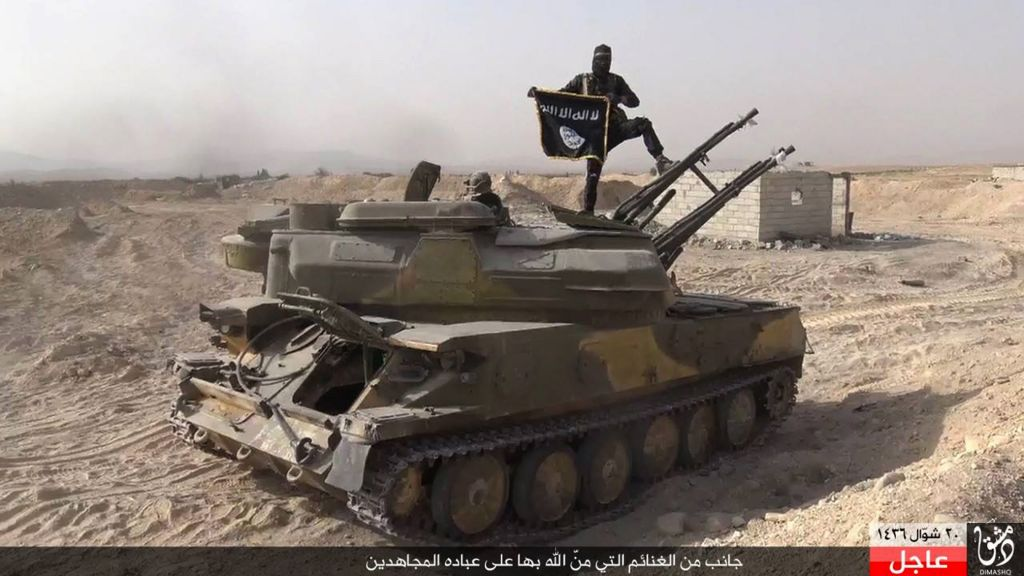 In this file photo released on Aug. 5, 2015, by the Rased News Network a Facebook page affiliated with Islamic State militants, an Islamic State militant holds the group's flag as he stands on a tank they captured from Syrian government forces, in the town of Qaryatain southwest of Palmyra, central Syria. (Rased News Network via AP, File)