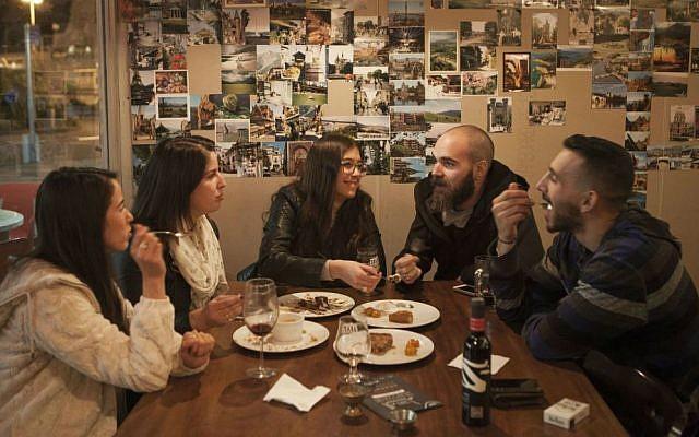 In this photo taken Tuesday, Dec. 8, 2015, Israelis enjoy a meal during an Arab Food Festival in Haifa, Israel. (AP Photo/Dan Balilty)
