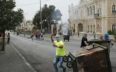 This Friday, Oct. 23, 2015 photograph shows Palestinians clashing with Israeli troops in front of the century-old Jacir Palace hotel in the West Bank city of Bethlehem. (AP Photo/Nasser Shiyoukhi)