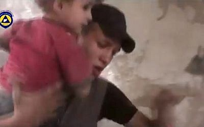 In this file image made from video posted online on Friday, Oct. 2, 2015, by Syrian Civil Defense, also known as the White Helmets, a volunteer search and rescue group, which has been verified and is consistent with other AP reporting, a paramedic rescues a child from the site of what witnesses said was a Russian airstrike in Douma, Syria. (Syria Civil Defense via AP video, File)