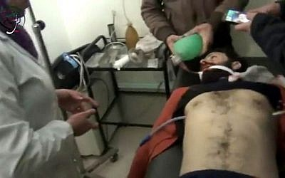 This image made from video made available by the Media Center in Moadamiyat al-Sham on Wednesday, Dec. 23, 2015, shows a medic helping a patient at a town clinic, after an attack, in Moadamiyeh, southwest of Damascus, Syria. (Media Center in Moadamiyat al-Sham via AP)