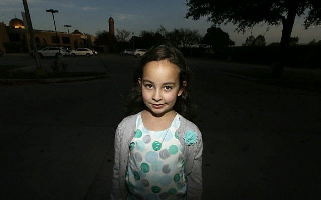 Sofia Yassini, 8, poses for a photo outside a mosque in Richardson, Texas, Friday, Dec. 11, 2015. (AP Photo/LM Otero)