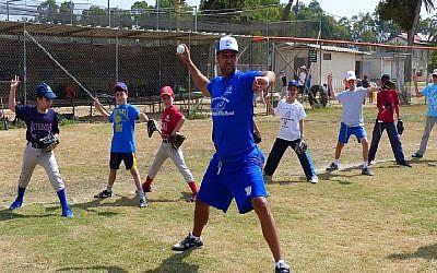 Nate Fish, director of the Israel Association of Baseball, demonstrating pitching to Israeli kids. (Margo Sugarman/IAB)