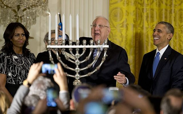 President Reuven Rivlin lights the menorah, joined by President Barack Obama, Michelle Obama, and Nechama Rivlin, during the first of two Hanukkah receptions the East Room of the White House in Washington, Wednesday, December 9, 2015. (AP Photo/Carolyn Kaster)