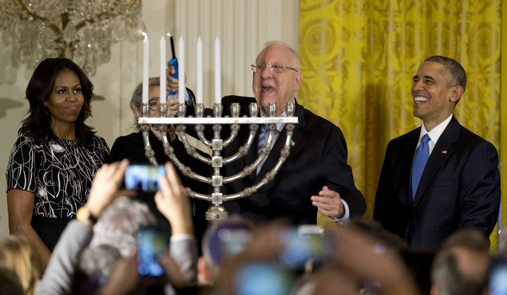 President Reuven Rivlin lights the menorah, joined by President Barack Obama, Michelle Obama, and Nechama Rivlin, during the first of two Hanukkah receptions the East Room of the White House in Washington, Wednesday, Dec. 9, 2015. (AP Photo/Carolyn Kaster)