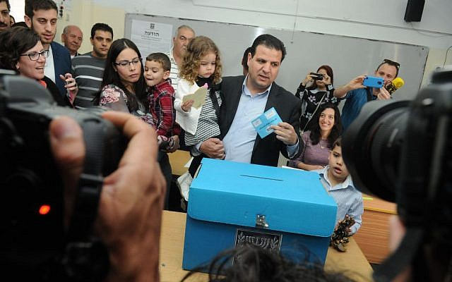Ayman Odeh, carrying one of his three children, casting his vote in Nazareth on Israel's Election Day, March 17, 2015. (Basal Awidat/Flash90)