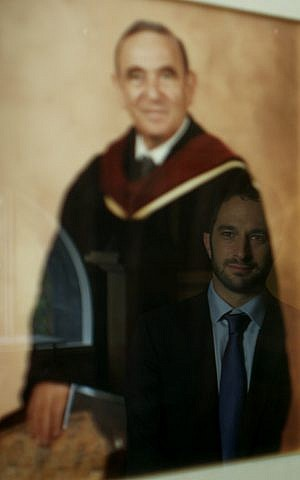 Filmmaker Aaron Wolf's image reflected in picture of his late grandfather Rabbi Alfred Wolf at Wilshire Boulevard Temple. (Howling Wolf Productions)