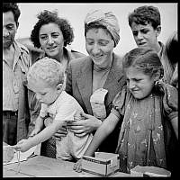 Women and children registering for the Fort Ontario Refugee Camp, August 1944. (public domain via wikipedia)