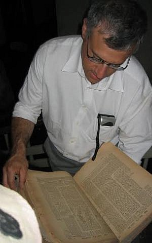 Former Pentagon official Harold Rhode studies an artifact from the Jewish community of Iraq in the basement of Saddam Hussein's secret police headquarters on May 6, 2003, Baghdad, Iraq. (Courtesy: Richard Gonzales)