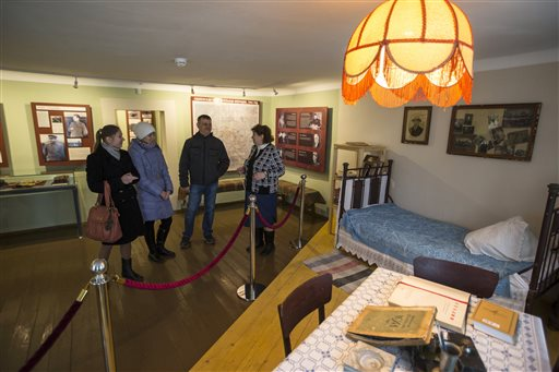 In this Wednesday, Dec. 9, 2015 photo, the director of the Stalin museum, Lydia Kozlova, right, speaks to visitors, in the museum in the village of Khoroshevo, west of Moscow, Russia. The Stalin museum was opened this year in this small village where the Soviet leader is said to have stayed the night on his only visit to the front during World War II. (AP Photo/Pavel Golovkin)