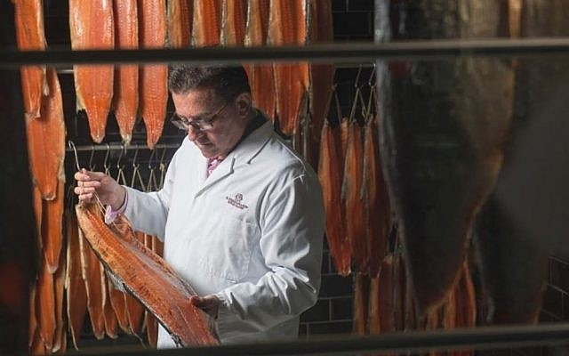 CEO Lance Forman examines a salmon fillet at Forman and Sons headquarters. (courtesy)