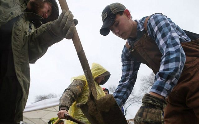 Jesse Nelson, left, 32, of Barnhart, Missouri, and Ryan Morris, 20, of Imperial, join other volunteers in making sandbags as the Mississippi River rises after several days of rain in Kimmswick, south of St. Louis, on Sunday, Dec. 27, 2015. (Cristina M. Fletes/St. Louis Post-Dispatch via AP)