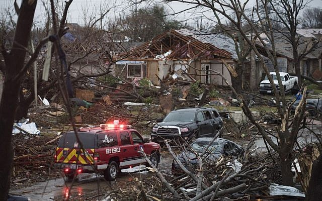 An emergency vehicle drives through a neighborhood in Rowlett, Texas, Sunday, December 27, 2015, the morning after it was struck by a tornado. (Photo by AP Photo/Rex C. Curry)