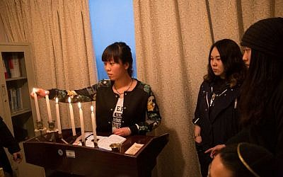 Members of the Kaifeng Chinese Jewish community light the menorah on the first night of Hanukkah, December 6, 2015. (Shavei Israel)