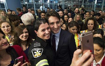 Canadian Prime Minister Justin Trudeau (center, right) poses for a selfie with workers before he greets refugees from Syria at Pearson International airport, in Toronto, on December 10, 2015. (Nathan Denette/The Canadian Press via AP)