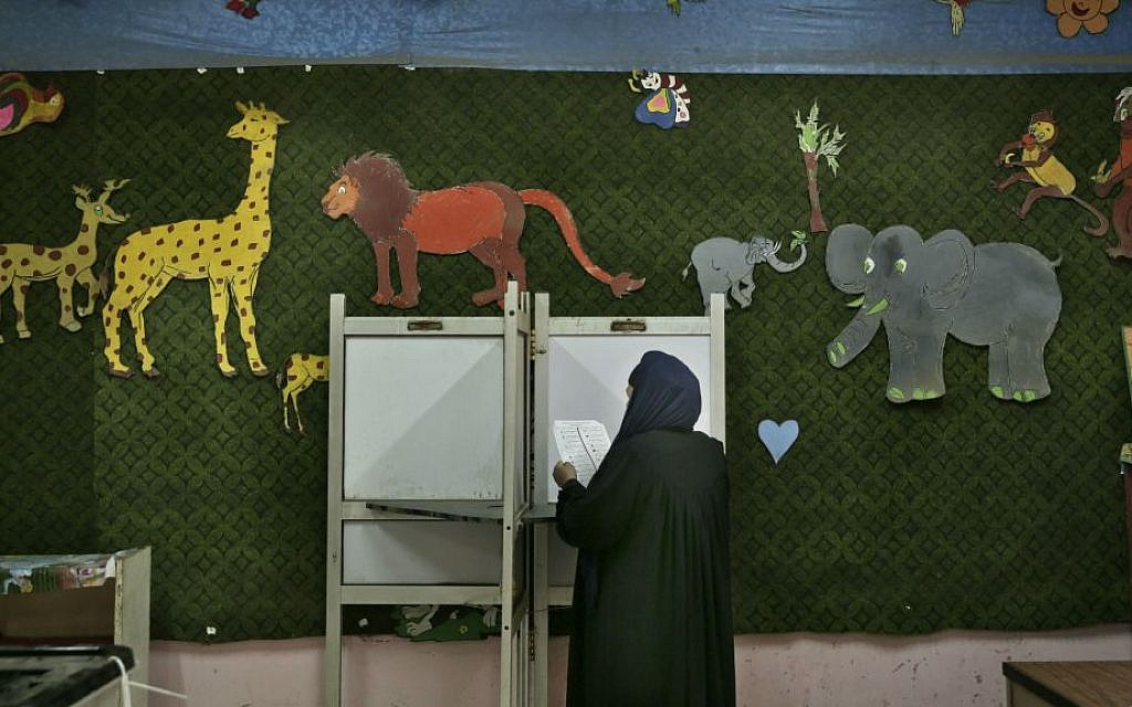 In this Sunday, Nov. 22, 2015 file photo, a woman reads a ballot inside a polling station for women during the second phase of the parliamentary elections in Qalyoubiya governorate, north of Cairo, Egypt. (AP Photo/Nariman El-Mofty, File)
