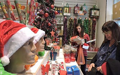 Customers shopping at Joy, a small Tel Aviv store that has been heckled repeatedly for selling Christmas and New Year's merchandise. (Ben Sales/JTA)
