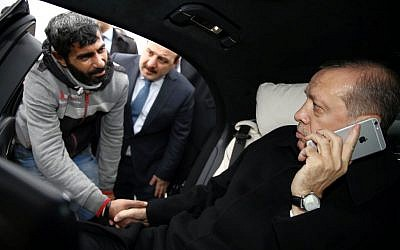 Turkish President Recep Tayyip Erdogan, right, takes Vezir Cakras by hand while speaking on his mobile phone inside his car stationed over the Bosporus Bridge in Istanbul, Friday, Dec. 25, 2015. Erdogan's office says the Turkish president has talked Cakras out of jumping off a bridge to commit suicide. (Yasin Bulbul/Presidential Press Service Pool via AP Photo)