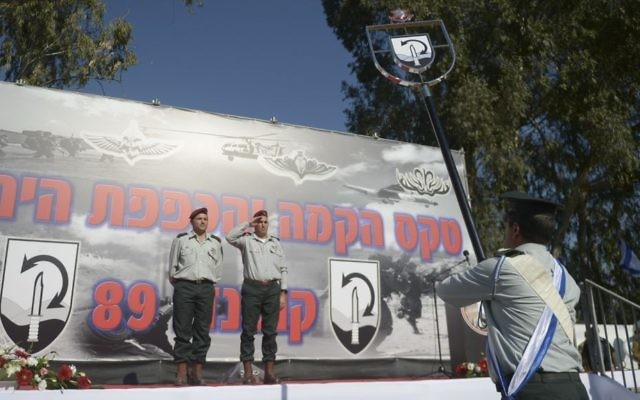 Col. David Zini and Brig. Gen. Uri Gordin receive the symbol of the IDF's newly formed Commando Brigade during a ceremony marking the unit's creation on December 27, 2015. (Yahav Trudler/IDF Spokesperson's Unit)