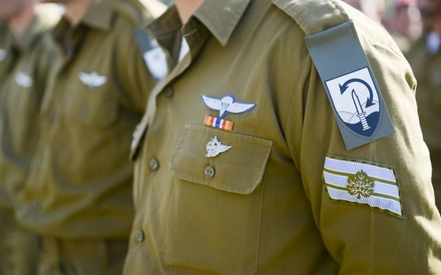 The new unit insignia for the Commando Brigade -- a knife on a background of mountains with a two-sided arrow signifying the unit's overseas reach -- is unveiled in a ceremony on December 27, 2015. (Yahav Trudler/IDF Spokesperson's Unit)