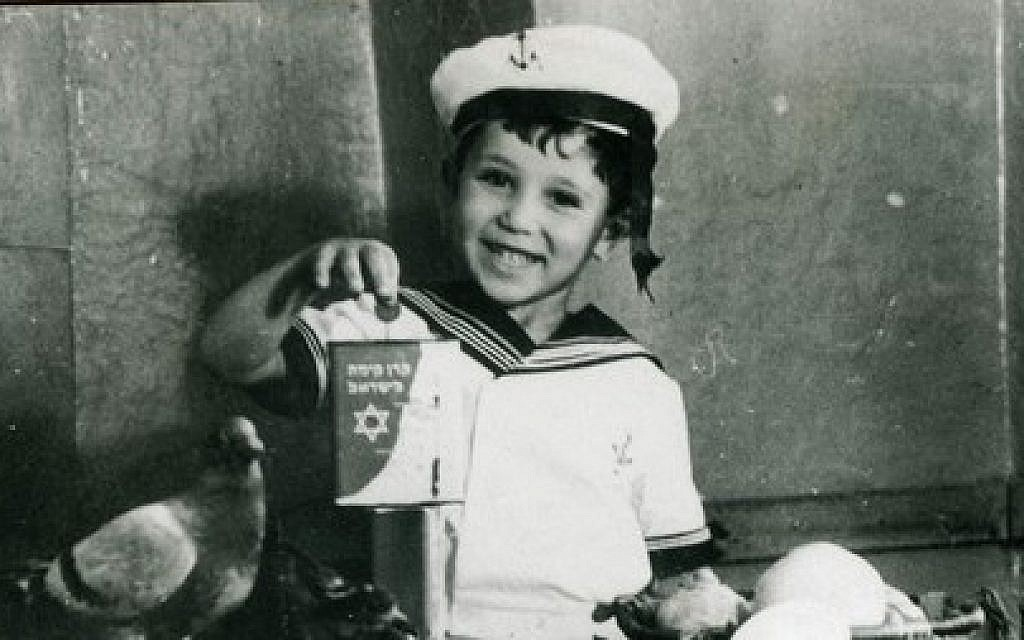 A child holds up a KKL-JNF blue box to collect donations in this undated photo. The blue box was one of the first ways to raise money for the fledgling KKL-JNF Jewish National Fund and was common in many Jewish homes. (Courtesy KKL-JNF)
