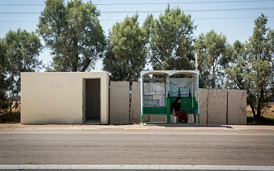 Illustrative photo of a woman waiting at a bus stop near a public bomb shelter, on July 6, 2015. (Miriam Alster/Flash90)