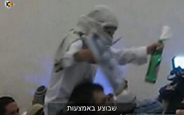 A far-right Israeli wedding-goer celebrates the murder of the Dawabsha family (screen capture: Channel 10)