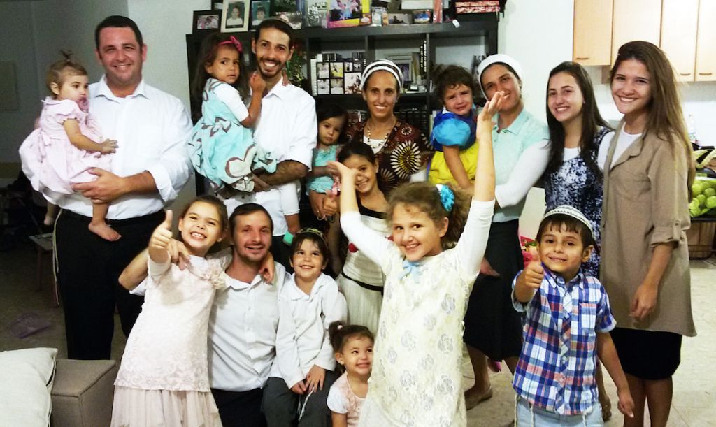 Fabio Erlich, standing left, with his family and other Brazilian emigres in the Israeli city of Modiin. (Courtesy of Erlich family)