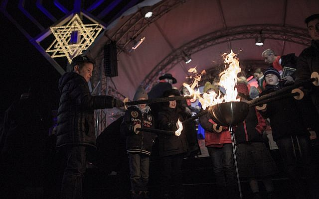 BERLIN, GERMANY - DECEMBER 06: Children light torches at the ceremony of the Hanukkah menorah lighting at a public Menorah ceremony near the Brandenburg Gate on December 6, 2015 in Berlin, Germany. The annual events are part of a worldwide Hanukkah campaign set into motion by the Lubavitcher Rebbe Rabbi Menachem M. Schneerson, of righteous memory. (Photo by Carsten Koall/Getty Images)