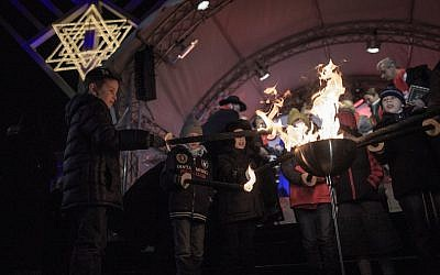 Children light torches at the ceremony of the Hanukkah menorah lighting at a public Menorah ceremony near the Brandenburg Gate on December 6, 2015 in Berlin, Germany. (Carsten Koall/Getty Images)