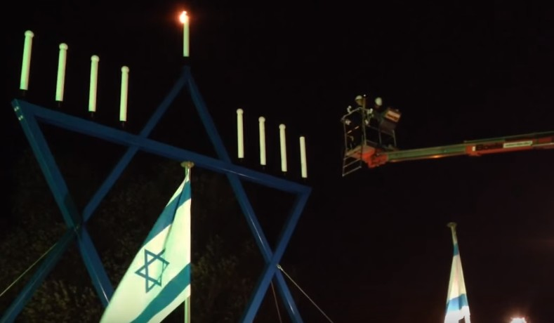 Dutch chief rabbi Binyomin Jacobs lights a giant menorah in Maastricht, the Netherlands, in 2013 (YouTube screen capture)