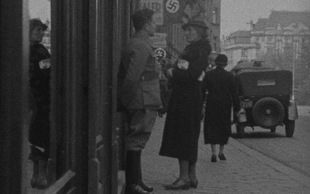 American Helen Baker confronted by a Nazi as she tries to enter a Jewish-owned store in Vienna, 1938, as seen in a film from the Ephemeral Films Project. (US Holocaust Memorial Museum)