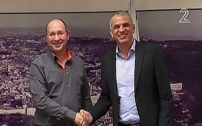 Histadrut labor federation leader Avi Nissenkorn (left) and Finance Minister Moshe Kahlon (right) shake hands during talks on December 21, 2015, aimed at avoiding a general strike over public-sector wages. (screen capture: Channel 2)