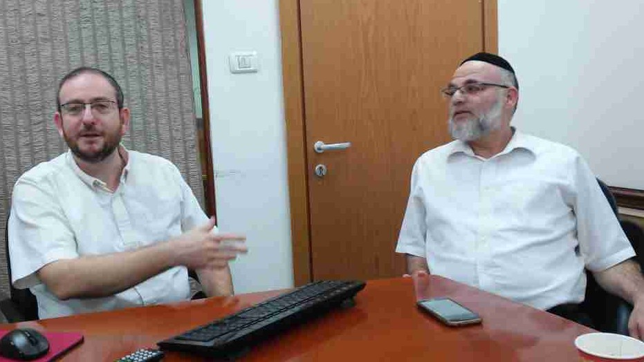 Staff members Tzvika Schreiber and Mordechai Feldstaine at the Kemach offices in Jerusalem (Simona Weinglass/The Times of Israel)