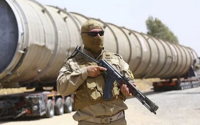 Kurdish security forces guard an oil refinery stolen by the Islamic State, before being brought on a truck to the Kalak refinery in the outskirts of Erbil, Iraq in 2014. (screen capture: YouTube)