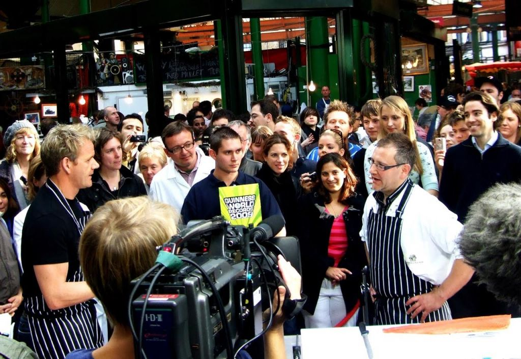 Master slicer Darren Matson (right) in striped apron facing (left) chef Gordon Ramsay as Matson makes an attempt to hold the world record for slicing a salmon fillet. (courtesy)