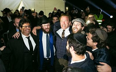 Former California governor Arnold Schwarzenegger dances with Chabad-Lubavitch rabbis at a public menorah lighting ceremony at the base of the Eiffel Tower in Paris on Sunday, December 6, 2015, the first night of the eight-day holiday. (Chabad.org/Thierry Guez)