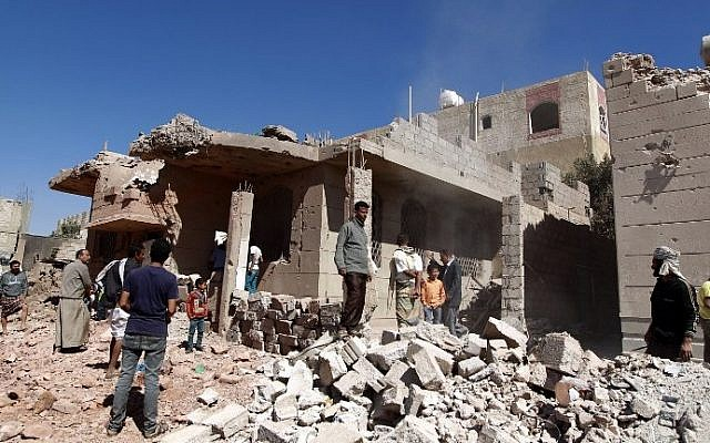 Yemeni men walk past a building, damaged during an air-strike by the Saudi-led coalition, in the capital Sanaa on November 29, 2015. (AFP Photo/Mohammed Huwais)