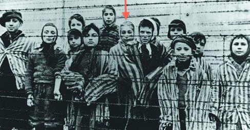 Marta Wise (center with red arrow) stands with a group of children behind the Auschwitz barbed wire. (courtesy)
