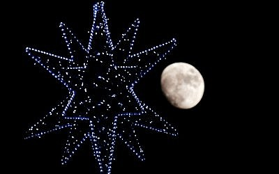 The moon rises behind the star of a Christmas Tree in central Rome on December 22, 2015. (AFP/TIZIANA FABI)