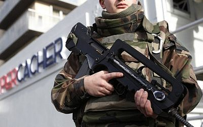 A French soldier stands guard during the posing of a commemorative plaque on the Hyper Cacher Jewish supermarket in Paris on January 4, 2016, in memory of four people killed during a hostage taking in the shop on January 9, 2015. (AFP / THOMAS SAMSON)