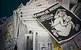A photo taken on January 4, 2016, at a printing house near Paris shows the cover of the latest edition of the French satirical magazine Charlie Hebdo, bearing a headline that translates as 'One year on: The assassin still at large,' in an edition to mark the first anniversary of the terror attack. (AFP/Martin Bureau)